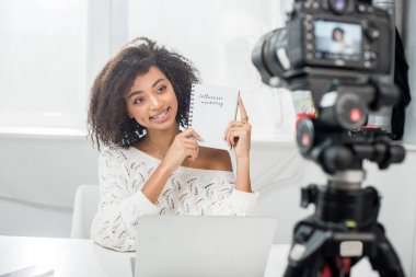 Selective focus of cheerful african american video blogger in braces holding notebook with influencer marketing lettering near digital camera stock vector