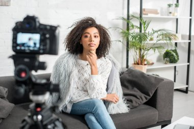 Selective focus of beautiful african american influencer looking at digital camera while sitting on sofa stock vector