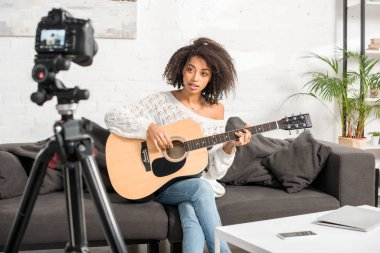 selective focus of beautiful african american influencer playing acoustic guitar near digital camera