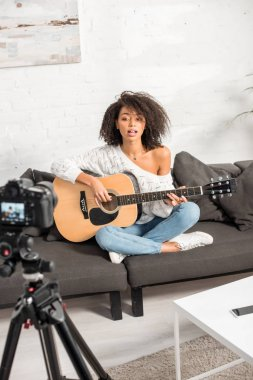 selective focus of young african american girl singing and playing acoustic guitar near digital camera