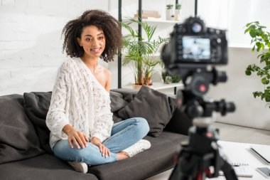 Selective focus of happy african american influencer sitting on sofa and looking at digital camera stock vector