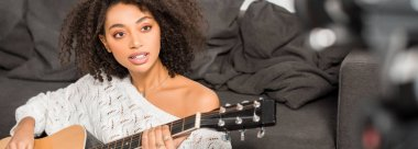 panoramic shot of young african american girl in braces playing acoustic guitar near digital camera in living room