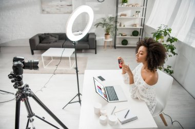 KYIV, UKRAINE - DECEMBER 10, 2019: african american influencer holding hair straightener near digital camera and laptop with ebay website stock vector