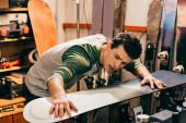 Schöne Arbeiterin berührt Snowboard in Reparaturwerkstatt