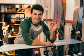 smiling worker showing ok and standing near snowboard in repair shop
