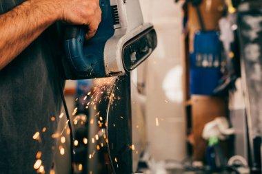 cropped view of worker repairing snowboard with belt sander in repair shop