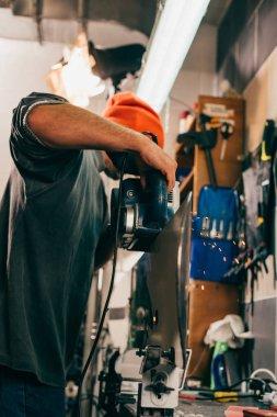 Worker repairing snowboard with belt sander in repair shop stock vector
