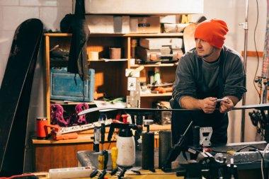 İşçi snowboard 'un yanında dikiliyor ve tamirhaneye bakıyor.