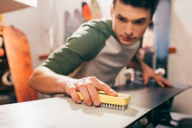 Selective focus of worker using brush on snowboard in repair shop stock vector