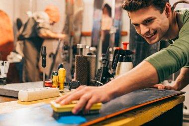 Smiling worker using brush on snowboard in repair shop stock vector