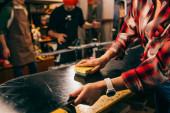Ausgeschnittene Ansicht eines Arbeiters, der in der Werkstatt Snowboard mit Pinsel poliert