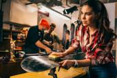 Selektiver Fokus des Arbeiters beim Polieren von Snowboard mit Pinsel in der Werkstatt