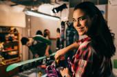 Selektiver Fokus des lächelnden Arbeiters beim Schrauben von Snowboard-Bindung an Snowboard in der Werkstatt