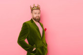 handsome man with crown in velour jacket looking at camera on pink background
