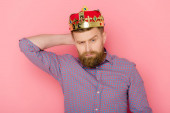 serious man with crown looking at camera on pink background