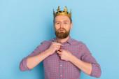 seriózní muž s korunou při pohledu na kameru na modrém pozadí