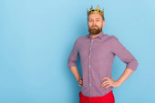 serious man with crown with hands on hips looking at camera on blue background