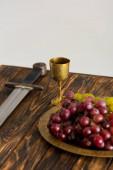 ősi csésze, kard és szőlő a fa asztalon elszigetelt szürke