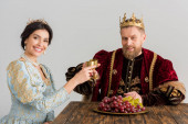 smiling queen and king with crowns clinking with cups isolated on grey