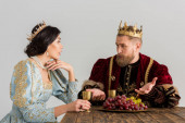 queen and king with crowns sitting at table and talking isolated on grey