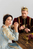 serious queen and king with crowns sitting at table isolated on grey