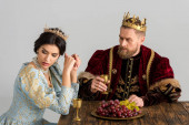 upset queen and king with crowns sitting at table isolated on grey