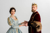 smiling queen and king with crowns holding hands isolated on grey