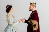 side view of queen and king with crowns holding hands isolated on grey