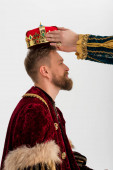 Fotografie cropped view of man putting crown on king on grey background