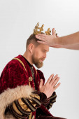 Fotografie cropped view of man putting crown on king with praying hands on grey background