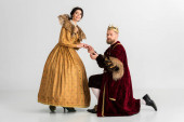 king with crown bending on knee and holding hand of smiling queen on grey background