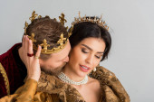 king with crown hugging and kissing attractive queen isolated on grey