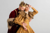 king with crown hugging attractive queen isolated on grey
