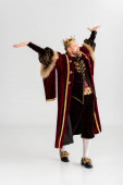boldog király koronával és kinyújtott kézzel szürke háttér