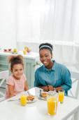 veselé africké americká matka a dcera při pohledu na kameru v blízkosti chutné palačinky
