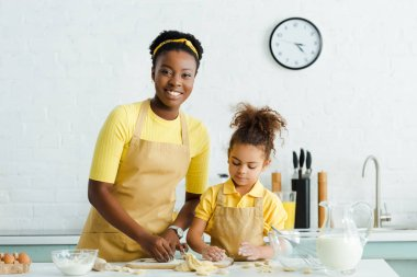 happy african american mother and cute daughter in apron sculpting raw dumplings in kitchen
