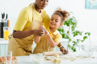 Selective focus of cute african american kid holding raw dough near mother and dumplings on cutting board stock vector