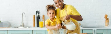 Panoramic shot of cheerful african american mother pouring milk in bowl near cute daughter and looking at camera stock vector