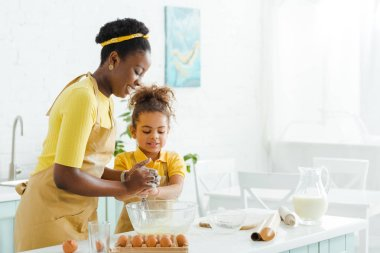 adorable african american kid and cheerful mother smiling while cooking in kitchen