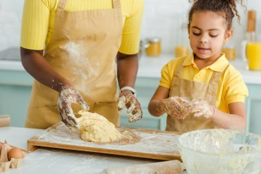 Cropped view of african american mother and daughter kneading dough stock vector