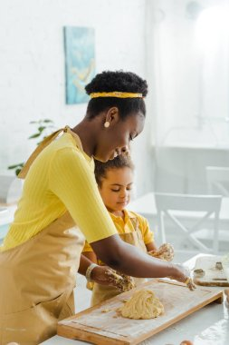 Happy african american mother and daughter kneading raw dough stock vector