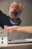 oříznutý pohled na agenta dávat klíče ženě v blízkosti karton dům model