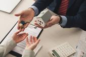 shora pohled realitní makléř dává klíče k ženě a drží karton dům model v kanceláři
