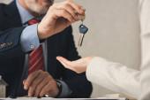 oříznutý pohled realitního makléře, který dává klíč ženě v úřadu