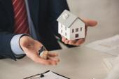 oříznutý pohled realitního makléře držícího klíče a papírový model domu v kanceláři