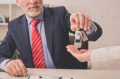 cropped view of bearded agent giving car key to client with cupped hand