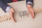 shora pohled agenta kladení rukou na stůl mezi dřevěné kostky a karton dům model