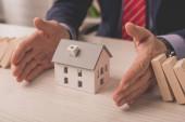 oříznutý pohled agenta, jak pokládá ruce na stůl mezi dřevěné kostky a papírový model domu