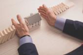 oříznutý pohled realitního makléře, jak pokládá ruce na stůl mezi dřevěné kostky a papírový model domu