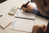 selective focus of agent writing in notebook with rent and buy lettering near money and calculator